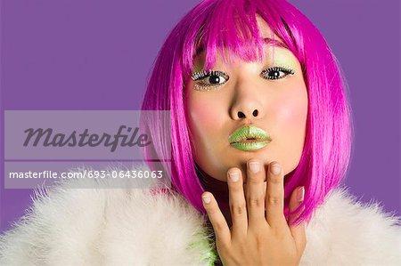 Porträt des jungen irre Frau in Rosa Perücke Blasen Kuss auf Lila Hintergrund