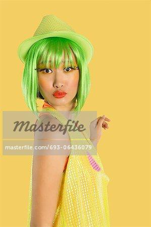 Portrait de jeune femme funky cheveux verts fronçant ses lèvres sur fond jaune