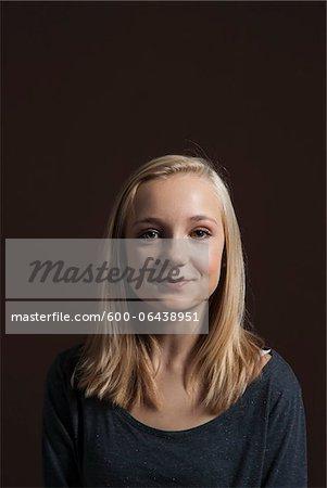 Portrait of Blond, Teenage Girl, Smiling at Camera, Studio Shot on Black Background