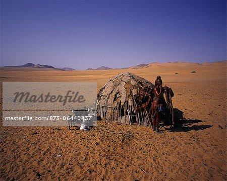 Portrait de femme Himba, debout près de cabane avec chèvres Namibie, Afrique