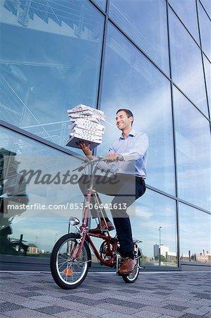 Homme avec les boîtes à pizza sur le vélo