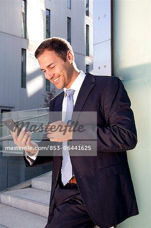 Homme d'affaires à la recherche sur téléphone cellulaire à l'extérieur de sourire