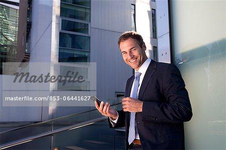 Homme d'affaires souriant avec téléphone cellulaire à l'extérieur