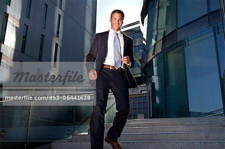 Homme d'affaires souriant marche dans les escaliers