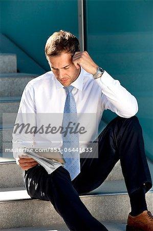 Homme assis avec tablet PC et le journal dans les escaliers