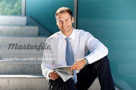 Homme d'affaires souriant assis avec tablet PC et le journal dans les escaliers