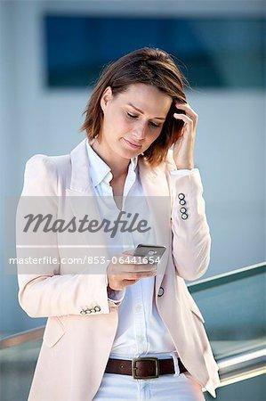Femme d'affaires en regardant son téléphone cellulaire