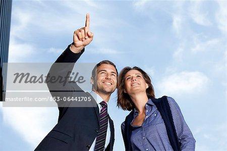 Homme d'affaires montrant femme d'affaires de quelque chose à l'extérieur