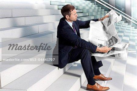 Journal de lecture homme d'affaires dans les escaliers