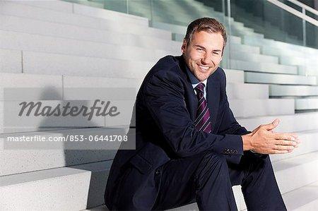 Homme d'affaires souriant assis sur les escaliers