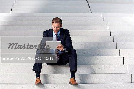 Homme d'affaires à l'aide de tablet PC dans les escaliers