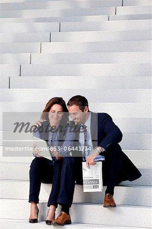 Homme d'affaires et femme d'affaires avec tablet PC et le journal dans les escaliers