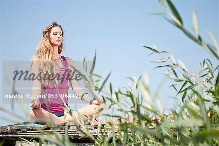 Blonde jeune femme pratique l'yoga dans un lac
