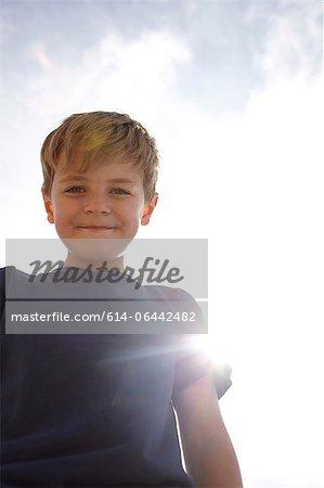 Vue d'angle faible de garçon dans la lumière du soleil