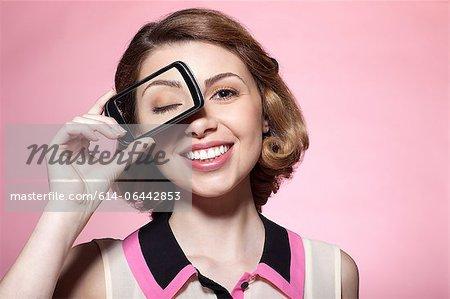 Woman with smartphone over eye