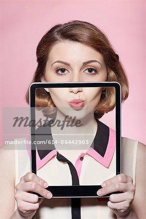 Femme couvrant la moitié de son visage avec tablette numérique