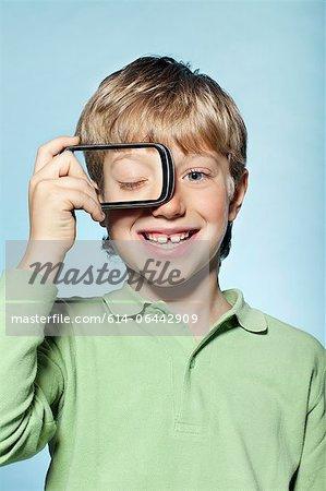 Boy holding smartphone over eye