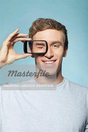 Man holding smartphone over eye