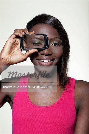 Teenage girl holding smartphone over eye