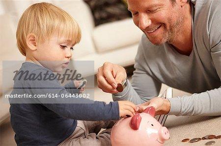 Vater und Sohn setzen Münzen im Sparschwein