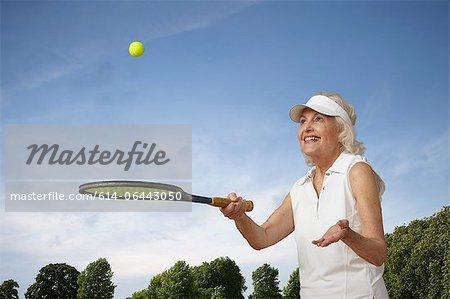 Senior woman bouncing tennis ball on rocket