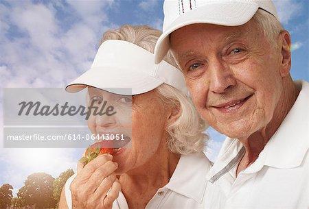 Couple de tennis Senior manger des fraises