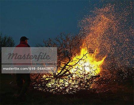 Homme debout en face de la nuit de Walpurgis bonfire