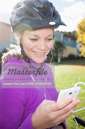 Glücklich weibliche Radfahrer durch Handy Musik hören