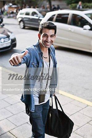 Portrait de jeunes heureux homme gesticulant comme il porte sac sport