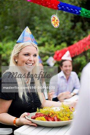 Glückliche junge Frau Teller voll von gekochten Hummer am Esstisch während Kräftskiva übergeben