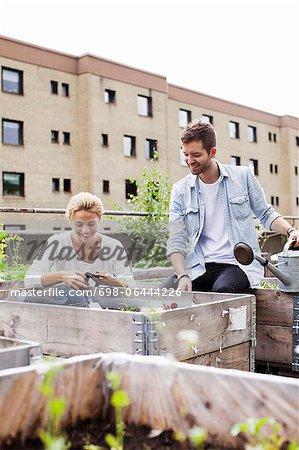 Heureux jeune couple de race blanche au jardin urbain
