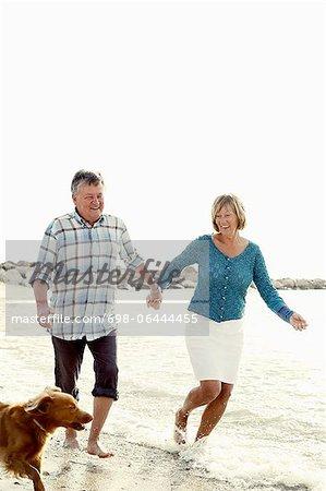 Glückliches Paar mit Hund am Strand genießen