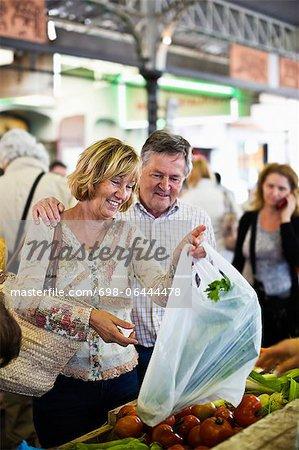 Heureux couple shopping au marché aux légumes