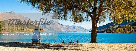 Panorama d'un touriste relaxant par lac Wakatipu en automne à Queenstown, Otago, île du Sud, Nouvelle-Zélande, Pacific
