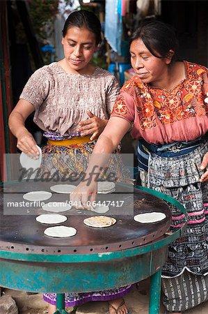 Mayan women baking tortillas in the market at Santiago Sacatepequez, Guatemala, Central America