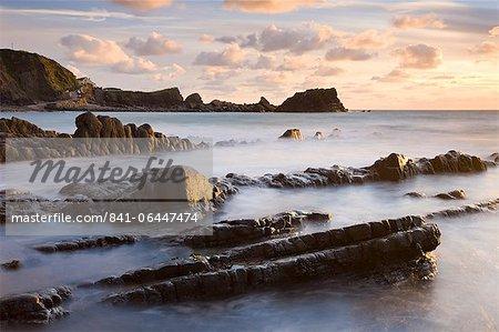 Soleil de fin de soirée brille sur les roches mouillées à Hartland Quay, North Devon, Angleterre, Royaume-Uni, Europe