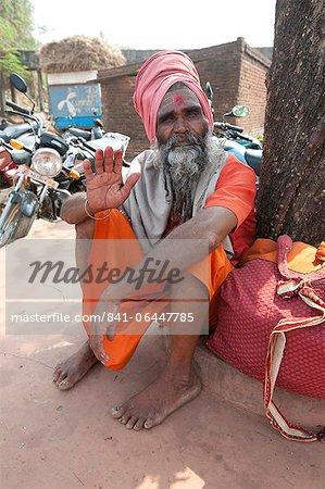 Travelling saddhu dressed in holy colour orange, resting beneath a village tree, Bhubaneshwar, Orissa, India, Asia