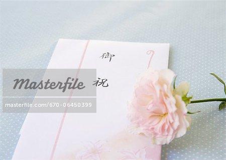 Congratulatory gift envelope and a rose