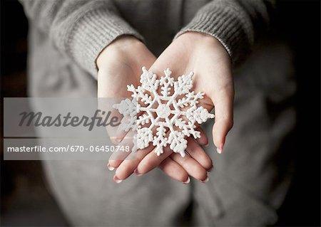 Frau hält einen Schnee Kristall Schmuck
