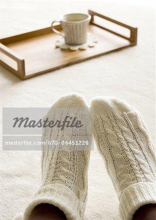 Ingwer-Tee auf einem Tablett und Füße tragen Socken