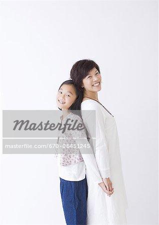 Mère et fille debout dos à dos