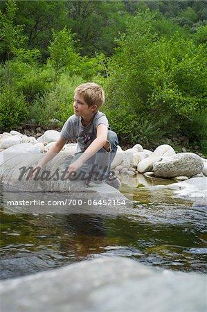 Boy Sitting on Rock by River