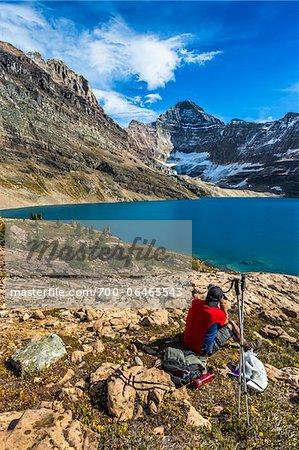 Hiker Resting at McArthur Lake, Yoho National Park, British Columbia, Canada