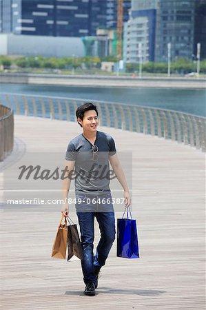 Young man walking on boardwalk holding shopping bags