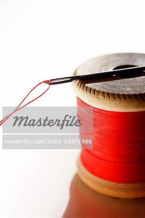 Spool of thread with needle, studio shot