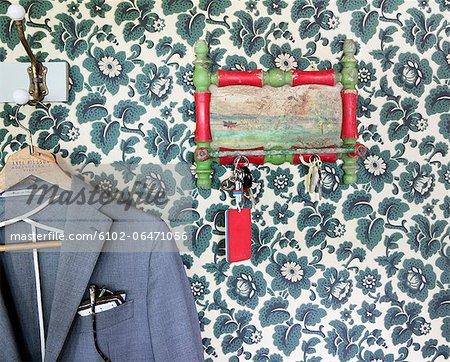 Keys hanger and jacket against floral wallpaper