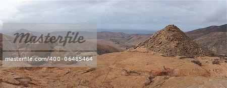 Panorama of volcanic hills, Fuerteventura, Canary Islands. Ocean in background.