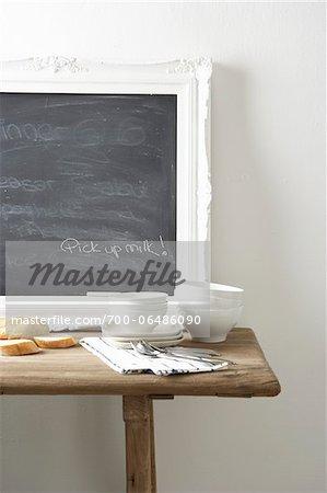 """Chalkboard in kitchen with note """"pick up milk"""" written on it"""