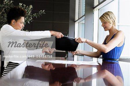 Businesswomen fighting over folder