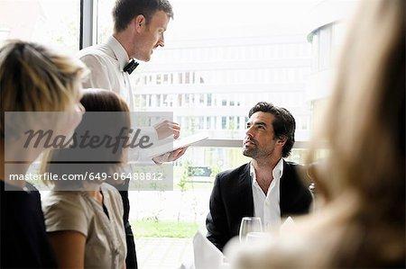 Waiter taking businessmans order